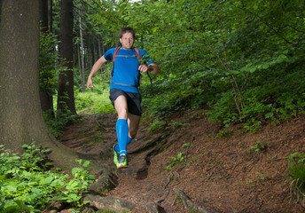 man running on the trail down the hill in the forest