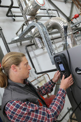 Technician checking heat pump intensity with electronic device