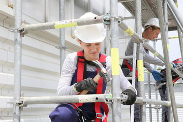 Young woman in professional training working on scaffolding