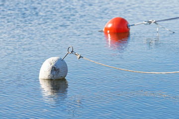 White marker bouy in foreground and a red one in the back