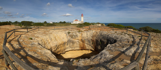 Panorama of a huge hole in carbonate cliff rocks and protection fences. Blue clouded sky and Carvoeiro lighthouse in the background. Algarve, Portugal.