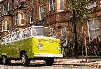Old vintage green van parked in a street with victorian houses