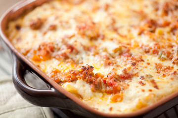 Fresh baked classic Lasagna in casserole dish. Layered with long simmered ragu, béchamel sauce, noodles and quality parmesan cheese.