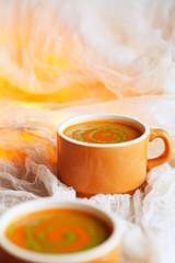 Halloween Tomato Soup and Pesto Swirls with gauzy background decor and Halloween orange lights.