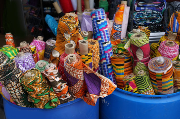 bins of colorful rolls of fabric outside a shop