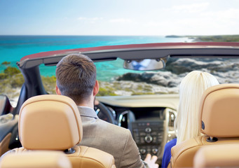 couple driving in cabriolet car over sea shore