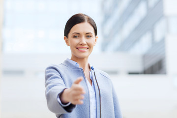 smiling businesswoman giving hand for handshake