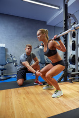 man and woman with bar flexing muscles in gym