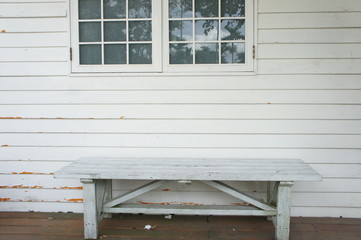 The white bench in front of white wood wall