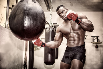 African male boxer punching ball wearing boxing gloves