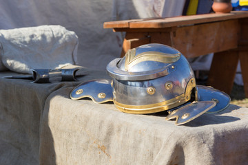 Ancient Roman helmet and ax on table