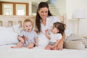 Happy mother with cute babies boy and girl