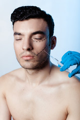 Filling wrinkles, crow's feet, injection of hyaluronic acid . Portrait of a handsome man during the treatment of facial wrinkles filling, Cosmetic is injected into facial skin cosmetics