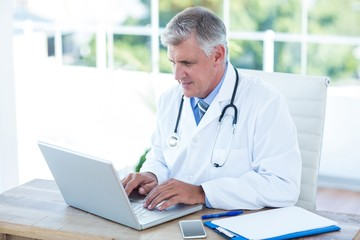 Serious doctor working on laptop at his desk