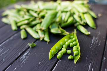 Fresh green peas scattered on the beautiful old wooden background