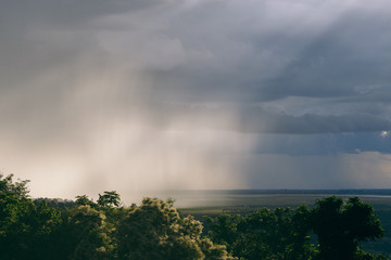 An intense rain storm approaches, its rain clouds intercepted by the sunrays of the sunset, making for a fantastic view. Registered from a mountain top, in the midst of the jungle, in Cambodia.