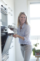 Smiling woman at oven in kitchen