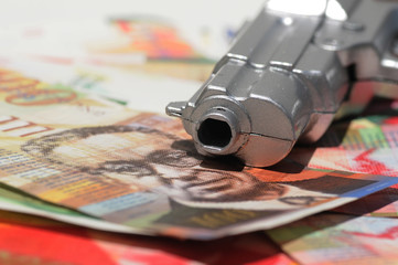 Focusing on a Gun's muzzle on a pile of new Israeli Shekels (NIS