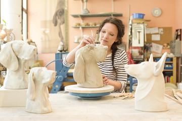 Potter in workshop working on dog figurine