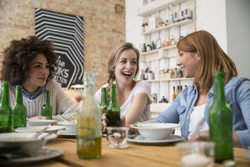 Happy female friends sitting at dining table with beer bottles