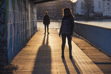 Germany, Berlin, teenage couple standing under a bridge at evening sunlight