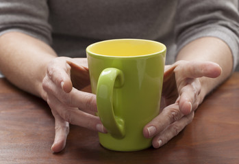 closeup on woman's hands thinking at breakfast with a cup of coffee