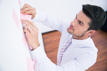 Businessman looking at sticker on wall