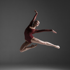 Young beautiful modern style dancer jumping on a studio