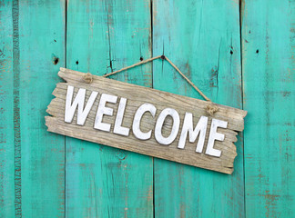 Welcome sign hanging on rustic background