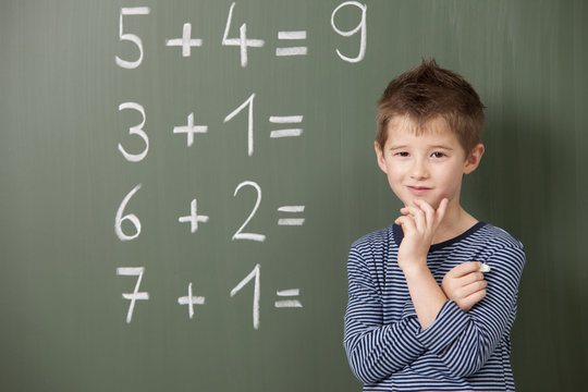 Schoolboy at blackboard with arithmetic problems