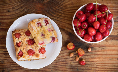 Ripe organic homegrown cherries and cherry cake, on wooden background