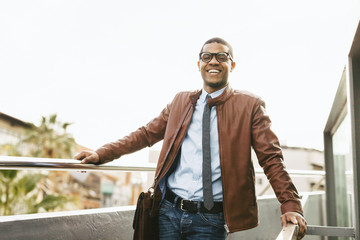 Portrait of laughing businessman wearing leather jacket and glasses