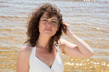 Woman brunette with curly hair on the beach