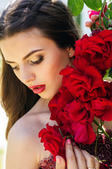 Fashion portrait of beautiful woman is posing near roses