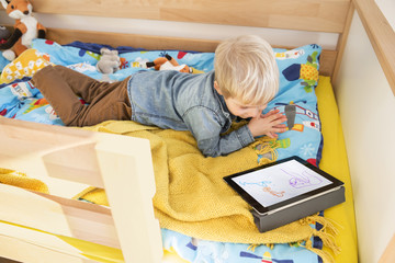 Little boy lying on his bed looking at digital tablet with child's drawing