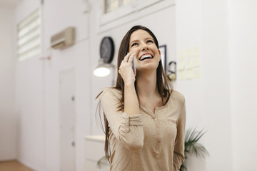 Young female entrepreneur telephoning with smartphone at home office