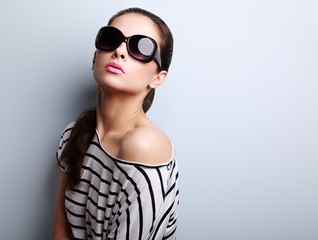 Style female model posing in fashion sun glasses and modern blou