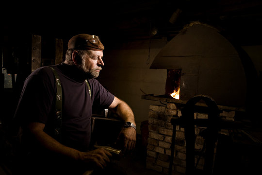 Blacksmith in workshop lost in thought
