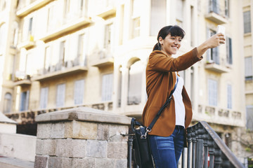 Spain, Barcelona, smiling businesswoman taking selfie with smartphone