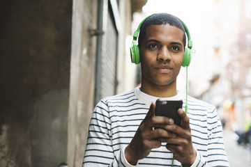 Spain, Barcelona, portrait of smiling young man hearing music with green headphones on street