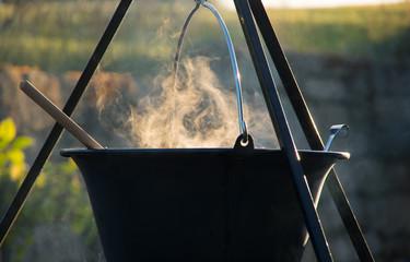 Dampfender Kessel über dem Lagerfeuer