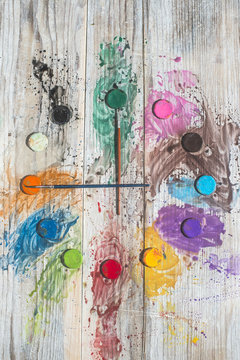 Watercolor paints and brushes forming a clock