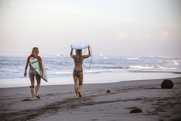 Indonesia, Bali, two women carrying surfboards on the beach