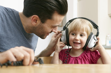 Father and daughter listening to music with headphones