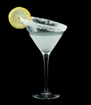 Lemon Drop Martini is a cocktail that contains vodka citron, triple sec, fresh lemon juice and is rimmed with sugar and garnished with a slice of lemon. Isolated on black.