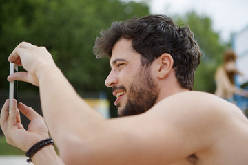 Young man taking cell phone picture outdoors