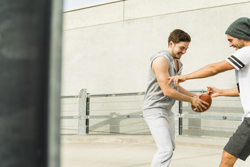 Two young men playing with football on parking level