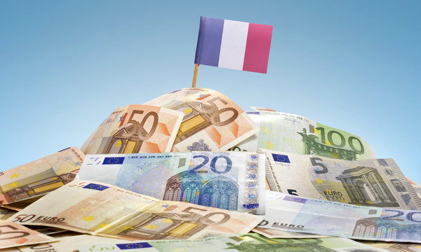Flag of France sticking in a pile of various european banknotes.