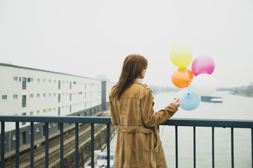 Young woman on bridge holding bunch of balloons