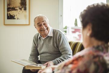 Senior man with photo album at home